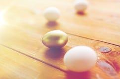 Κλείστε επάνω των χρυσών και άσπρων αυγών Πάσχας στο ξύλο Στοκ Εικόνες