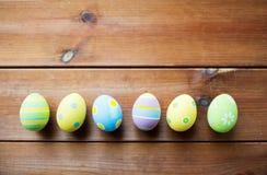 Κλείστε επάνω των χρωματισμένων αυγών Πάσχας στην ξύλινη επιφάνεια Στοκ Φωτογραφία