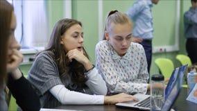 Κλείστε επάνω των όμορφων θηλυκών φοιτητών πανεπιστημίου που κάθονται μαζί στο γραφείο στην τάξη και που χρησιμοποιούν τους υπολο απόθεμα βίντεο