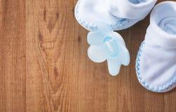 Κλείστε επάνω των bootees μωρών και soother για νεογέννητο στοκ φωτογραφίες