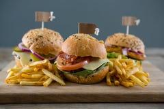 Κλείστε επάνω των burgers με τις τηγανιτές πατάτες που εξυπηρετούνται στον τέμνοντα πίνακα Στοκ Εικόνες