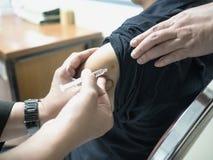 Κλείστε επάνω υπομονετικού παίρνοντας έναν εμβολιασμό στο νοσοκομείο Στοκ Εικόνες