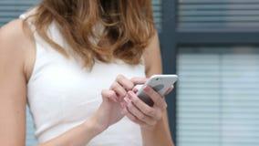 Κλείστε επάνω, χρησιμοποιώντας Smartphone από το όμορφο κορίτσι, έξω από το γραφείο απόθεμα βίντεο
