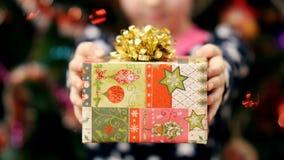 Κλείστε επάνω δύο χεριών παιδιών κρατώντας ένα δώρο Χριστουγέννων σε ένα όμορφο χρωματισμένο περιτύλιγμα εγγράφου με ένα χρυσό τό φιλμ μικρού μήκους