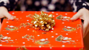 Κλείστε επάνω δύο χεριών παιδιών κρατώντας ένα δώρο Χριστουγέννων σε ένα όμορφο χρωματισμένο περιτύλιγμα εγγράφου με ένα χρυσό τό απόθεμα βίντεο