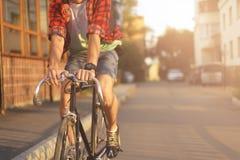 Κλείστε επάνω hipster στο ποδήλατο στην πόλη στο ηλιοβασίλεμα Στοκ Εικόνες
