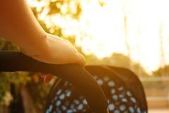 Κλείστε επάνω mom τον ωθώντας περιπατητή στο πάρκο με το ηλιοβασίλεμα Στοκ φωτογραφία με δικαίωμα ελεύθερης χρήσης