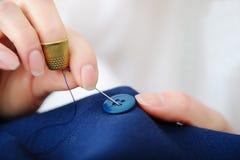 Κλείστε επάνω seamstress τα δάχτυλα που ράβουν το κουμπί στο εργαστήριο Στοκ Φωτογραφίες