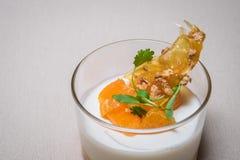 Κλείστε επάνω Tangerine γιαουρτιού σε ένα φλυτζάνι Στοκ Φωτογραφίες