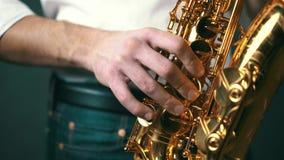Κλείστε κλειδωμένος κάτω από τον πυροβολισμό του saxophone παιχνιδιού μουσικών τζαζ στο στούντιο απόθεμα βίντεο