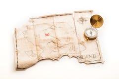 Κλείστε μέχρι τη χρυσή ναυτική πυξίδα στον παλαιό εκλεκτής ποιότητας χάρτη με το πλαστό νησί του θησαυρού πειρατών Στοκ φωτογραφίες με δικαίωμα ελεύθερης χρήσης