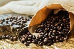 Κλείστε τα επάνω ψημένα φασόλια καφέ στις τσάντες εγγράφου στο ξύλινο υπόβαθρο Στοκ φωτογραφία με δικαίωμα ελεύθερης χρήσης