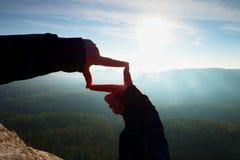 Κλείστε τα χέρια αποτελεί τη χειρονομία πλαισίων Μπλε misty δύσκολη αιχμή φυσητήρων κοιλάδων Ηλιόλουστη χαραυγή άνοιξη Στοκ Φωτογραφίες