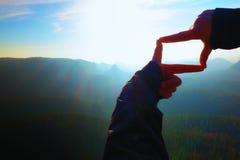 Κλείστε τα χέρια αποτελεί τη χειρονομία πλαισίων Μπλε misty δύσκολη αιχμή φυσητήρων κοιλάδων Ηλιόλουστη χαραυγή άνοιξη Στοκ εικόνες με δικαίωμα ελεύθερης χρήσης