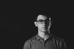 Κλείστε τον επάνω χαμογελώντας νέο επιχειρηματία που φορά Eyeglasses, εξετάζοντας τη κάμερα στο γκρίζο κλίμα τοίχων με το διάστημ Στοκ Εικόνες
