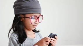Κλείστε το αυξημένο ασιατικό μικρό κορίτσι χρησιμοποιώντας το κινητό smartphone και παρουσιάζοντας αντίχειρες απόθεμα βίντεο