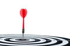 Κλείστε το αυξημένο κόκκινο βέλος βελών στο κέντρο του dartboard που απομονώνεται επάνω Στοκ φωτογραφία με δικαίωμα ελεύθερης χρήσης