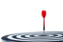 Κλείστε το αυξημένο κόκκινο βέλος βελών στο κέντρο του dartboard που απομονώνεται επάνω Στοκ Εικόνα
