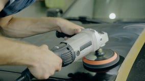 Κλείστε το αυξημένο μαύρο αυτοκίνητο στιλβωτικής ουσίας εργαζομένων με τα ειδικά εργαλεία φιλμ μικρού μήκους