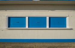 Κλειστά μπλε παραθυρόφυλλα στο περίπτερο στο κτήριο κρέμας Στοκ Εικόνα