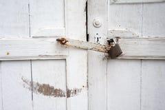 Κλειστή αντίκα πόρτα που χρωματίζεται με άσπρο και που κλειδώνεται με το σκουριασμένο lat στοκ εικόνες