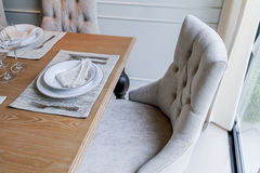 Κλειστή επάνω συμπαθητική να δειπνήσει καρέκλα με τα ξύλινα σύνολα πινάκων και πιάτων Στοκ εικόνα με δικαίωμα ελεύθερης χρήσης