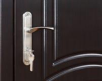 Κλειστή σκοτεινή καφετιά ξύλινη λαβή πορτών με την κλειδαριά Στοκ Φωτογραφία