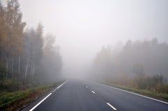 Κλειστός λόγω ομίχλης δρόμος μέσω του δάσους φθινοπώρου Στοκ Φωτογραφίες