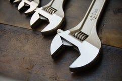 Κλειδί ή διευθετήσιμο γαλλικό κλειδί στο ξύλινο πίσω έδαφος, βασικά εργαλεία χεριών Στοκ Εικόνα
