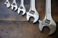 Κλειδί ή διευθετήσιμο γαλλικό κλειδί στο ξύλινο πίσω έδαφος, βασικά εργαλεία χεριών Στοκ Εικόνες