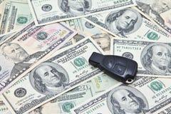 Κλειδί αυτοκινήτων του γερμανικού αυτοκινήτου στο σωρό των τραπεζογραμματίων αμερικανικών δολαρίων Στοκ Φωτογραφία