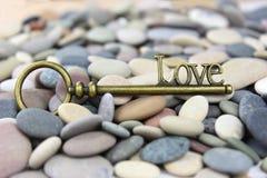 Κλειδί για την αγάπη σε ένα υπόβαθρο πετρών/χαλικιών παραλιών Στοκ Εικόνες