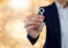 Κλειδί εκμετάλλευσης χεριών με το λαμπιρίζοντας ελαφρύ υπόβαθρο bokeh Στοκ εικόνα με δικαίωμα ελεύθερης χρήσης