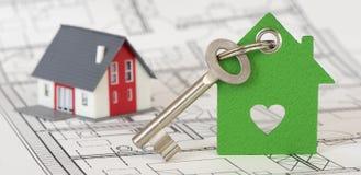 Κλειδί σπιτιών με το πρότυπο σπίτι πέρα από το σχέδιο κατασκευής Στοκ Φωτογραφία