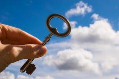 Κλειδί στο χέρι, υπόβαθρο ουρανού Στοκ Φωτογραφία