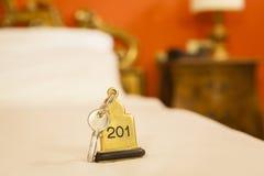 Κλειδί δωματίου ξενοδοχείου που βρίσκεται στο κρεβάτι με το μπρελόκ Στοκ Εικόνες