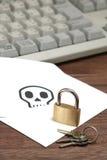 Κλειδαριά και κλειδιά μπροστά από το φάκελο με το κρανίο που γράφεται στο στηργμένος πληκτρολόγιο υπολογιστών καρτών Στοκ φωτογραφία με δικαίωμα ελεύθερης χρήσης