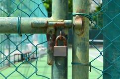 Κλειδαριά σκουριάς στον παλαιό πράσινο φράκτη πλέγματος καλωδίων μπροστά από το γήπεδο αντισφαίρισης Στοκ Εικόνες