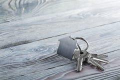 Κλειδιά για το σπίτι με το keychain στο άσπρο ξύλινο υπόβαθρο Στοκ Εικόνες