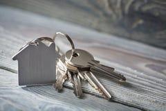 Κλειδιά για το σπίτι με το keychain στο άσπρο ξύλινο υπόβαθρο Στοκ Φωτογραφίες