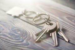 Κλειδιά για το σπίτι με το keychain στο άσπρο ξύλινο υπόβαθρο Στοκ Εικόνα