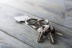 Κλειδιά για το σπίτι με το keychain στο άσπρο ξύλινο υπόβαθρο Στοκ φωτογραφίες με δικαίωμα ελεύθερης χρήσης