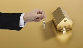 Κλειδιά εκμετάλλευσης χεριών με το χρυσό υπόβαθρο εδάφους και σπιτιών, την ακίνητη περιουσία και την έννοια ιδιοκτησίας Στοκ Φωτογραφία