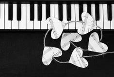 Κλειδιά πιάνων και καρδιές της μουσικής σε ένα μαύρο υπόβαθρο Στοκ εικόνα με δικαίωμα ελεύθερης χρήσης