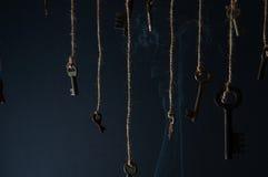 Κλειδιά που κρεμούν σε μια σειρά μεγάλα αντικείμενα ελέγχων ιστορικού περισσότερο ο άλλος παρόμοιος καπνός σειράς χαρτοφυλακίων μ στοκ εικόνες