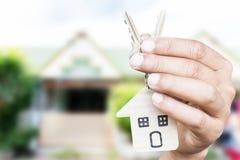 Κλειδιά σπιτιών εκμετάλλευσης στο σπίτι που διαμορφώνεται keychain μπροστά από ένα νέο ho Στοκ εικόνα με δικαίωμα ελεύθερης χρήσης