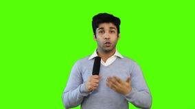 Κλειδώνω-στον πυροβολισμό της αρσενικής ομιλίας δημοσιογράφων TV σε ένα μικρόφωνο στο πράσινο υπόβαθρο απόθεμα βίντεο