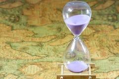 Κλεψύδρα, sandglass, χρονόμετρο άμμου, ρολόι άμμου στον παλαιό παγκόσμιο χάρτη θησαυρών Στοκ Εικόνες