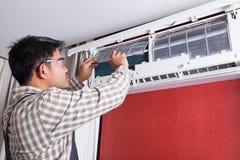 Κλιματισμός καθαρισμού ηλεκτρολόγων νεαρών άνδρων στο σπίτι πελατών στοκ φωτογραφία