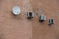 Κλιματιστικό μηχάνημα τρία στον παλαιό τοίχο οικοδόμησης και το δορυφορικό antena Στοκ εικόνες με δικαίωμα ελεύθερης χρήσης
